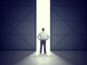 man standing in middle of garage doors