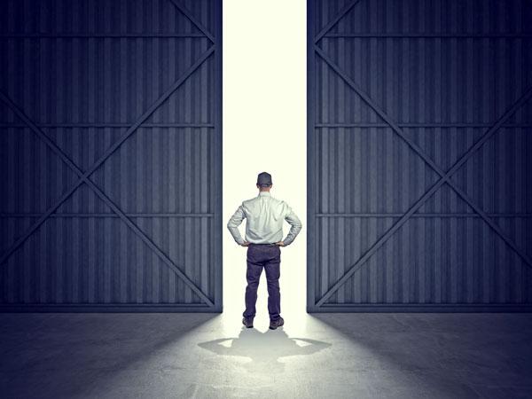 man standing in middle of garage doors