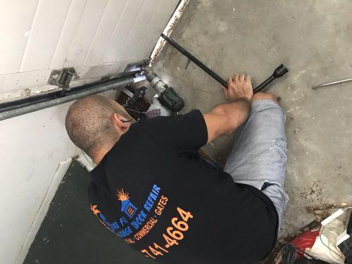Sure Fix Garage Door Repair expert repairing a stuck door 1