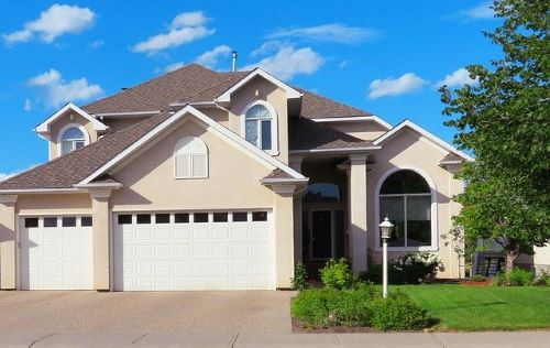 house with two white garage door installations