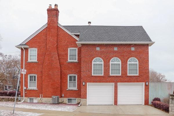 Two white new garage door installation on brick house