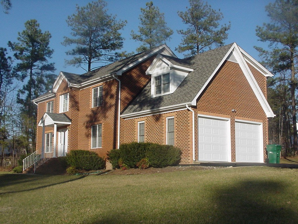 Virginia home with two popular style white garage doors